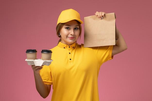 ピンクの机の上の笑顔でプラスチック製の茶色のコーヒーカップ食品パッケージを保持している黄色の制服黄色のケープの正面図女性宅配便