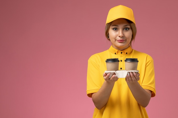 ピンクの机の上にプラスチック製の茶色のコーヒーカップを保持している黄色の制服黄色のケープの正面図女性宅配便制服配達作業色