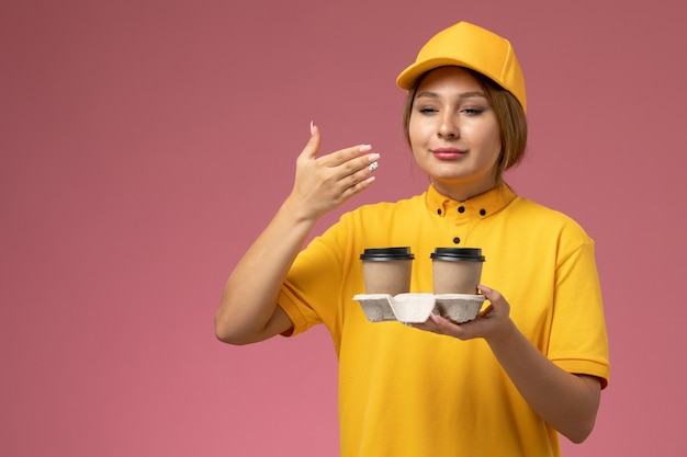 ピンクの机の上でそれらをかぐプラスチックの茶色のコーヒーカップを保持している黄色の制服黄色のケープの正面図女性宅配便制服配達女性の色