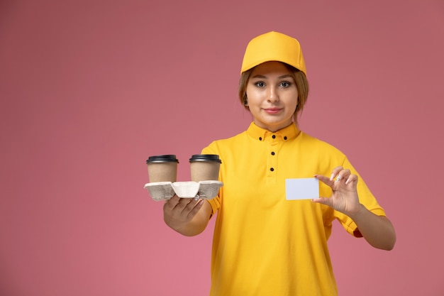 ピンクの机の上のプラスチック製の茶色のコーヒーカップwhtieカードを保持している黄色の制服黄色のケープの正面図女性宅配便制服配達女性の色