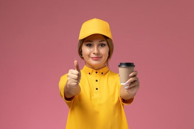 Вид спереди женщина-курьер в желтой униформе, желтой накидке, держащей пластиковую кофейную чашку на розовом фоне.