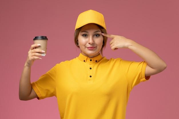 ピンクの背景にプラスチック製のコーヒーカップを保持している黄色の制服黄色のケープの正面図女性宅配便