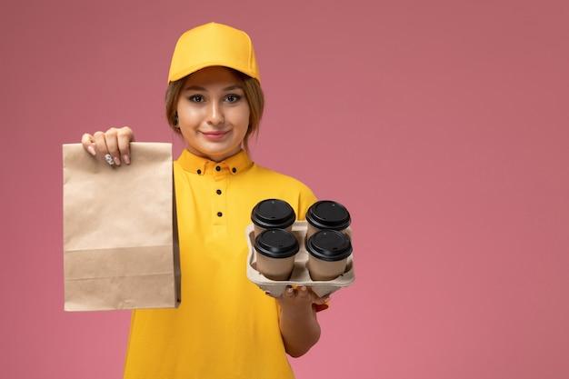 ピンクの背景にプラスチック製のコーヒーカップ食品パッケージを保持している黄色の制服黄色のケープの正面図女性の宅配便制服配達作業色の仕事