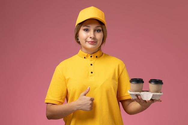 Вид спереди женщина-курьер в желтой униформе с желтым плащом держит пластиковые кофейные чашки на розовом фоне.
