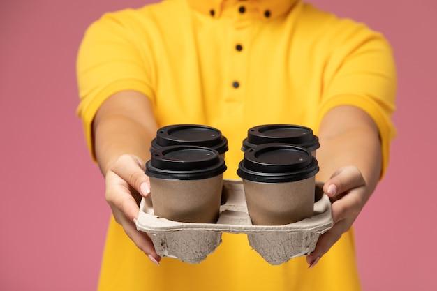 ピンクの机の上にプラスチック製のコーヒーカップを保持している黄色の制服黄色のケープの正面図女性宅配便制服配達作業色の仕事