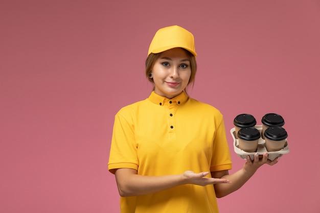 ピンクの背景にプラスチック製のコーヒーカップを保持している黄色の均一な黄色のケープの正面図の女性の宅配便均一な配達作業色