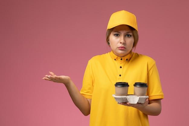 Вид спереди женщина-курьер в желтой форме желтой накидки с пластиковыми кофейными чашками на розовом фоне.