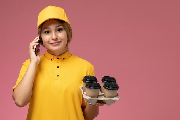 ピンクの背景の均一な配信色で電話で話しているプラスチック製のコーヒーカップを保持している黄色の制服黄色のケープの正面図女性宅配便