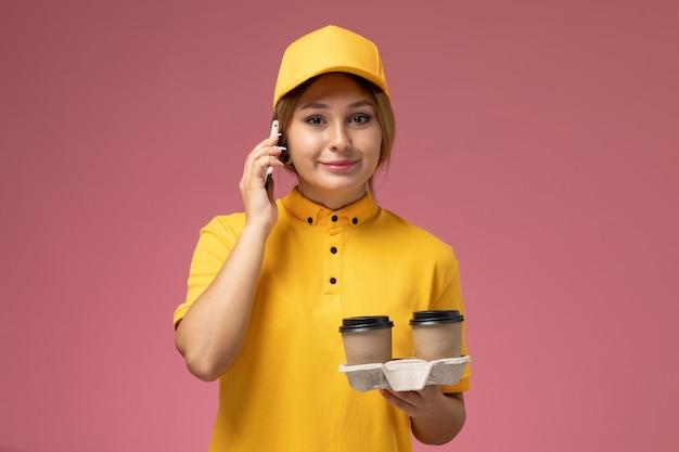 プラスチック製のコーヒーカップを保持し、ピンクの机の上の電話で話している黄色の制服黄色のケープの正面図女性宅配便制服配達作業カラージョブ