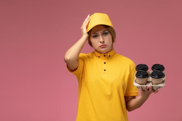 ピンクの背景に頭痛のあるプラスチック製のコーヒーカップを保持している黄色の制服黄色のケープの正面図女性宅配便制服配達作業色の仕事
