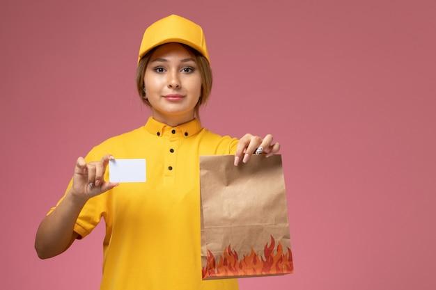 ピンクの背景に白いカードと食品パッケージを保持している黄色の制服黄色のケープの正面図女性宅配便制服配達作業色の仕事