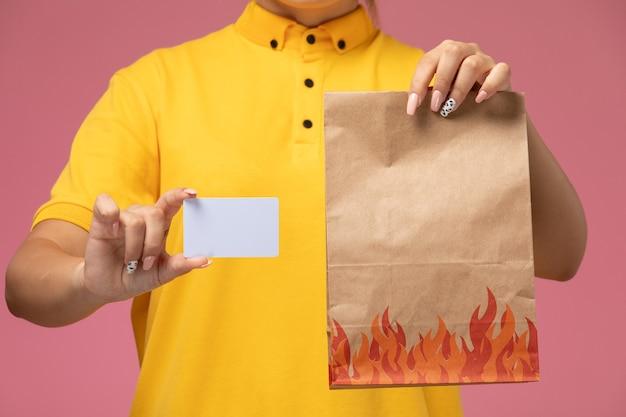 Вид спереди женщина-курьер в желтой униформе с желтым плащом держит белую карточку и продуктовый пакет на розовом столе.
