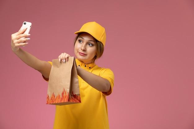 Женщина-курьер в желтой форме, желтая накидка, вид спереди, делает селфи с продуктовым пакетом на розовом фоне.