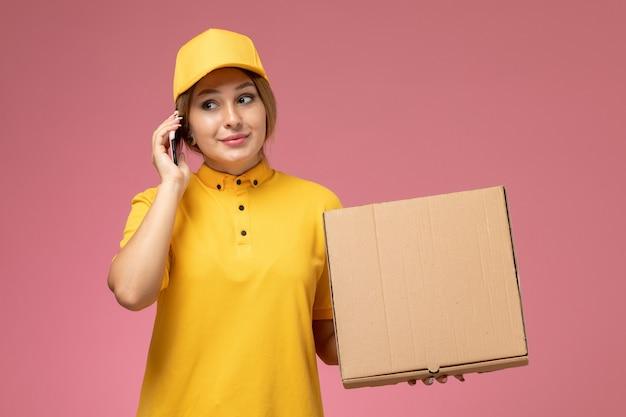 ピンクの背景の均一な配達の仕事で配達パッケージを保持している電話で話している黄色の制服黄色のケープの正面図の女性の宅配便