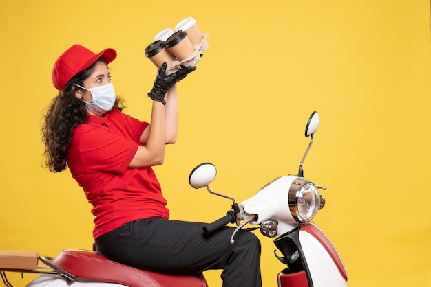 Front view female courier in mask on bike with coffee cups on yellow background worker service pandemic job woman delivery covid-