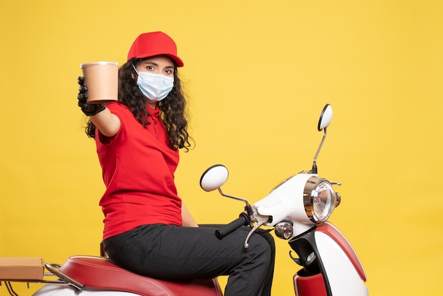 Front view female courier in mask holding delivery dessert on yellow background covid- job uniform worker service work delivery