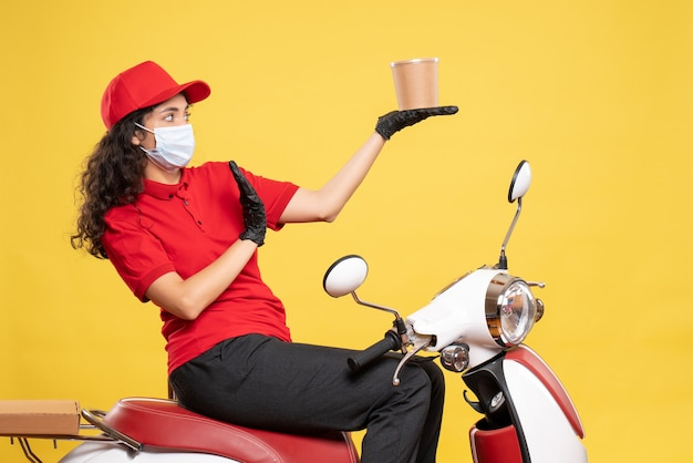 Front view female courier in mask holding delivery dessert on yellow background covid- job uniform worker work delivery