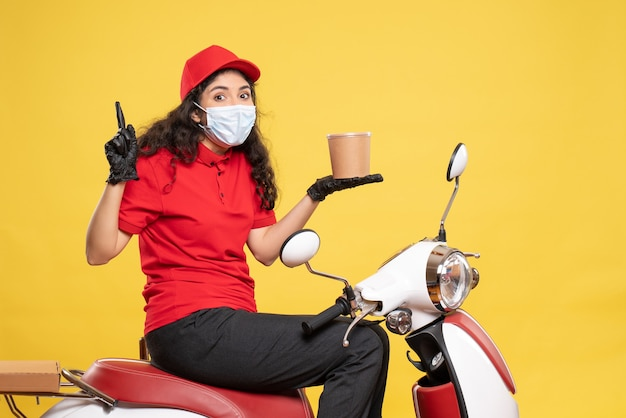 Front view female courier in mask holding delivery dessert on yellow desk covid- job uniform worker service pandemic delivery