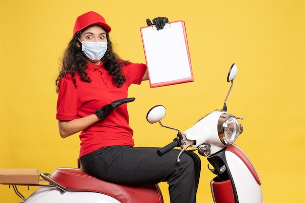 Front view female courier in mask holding file note on yellow background covid- job delivery uniform worker service work pandemic