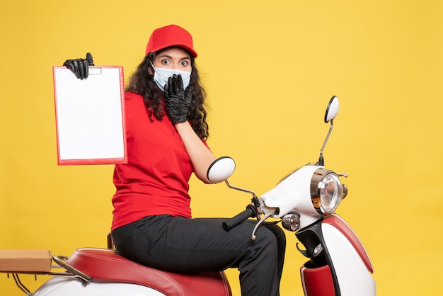 Front view female courier in mask holding file note on yellow background covid- job uniform service work pandemic delivery