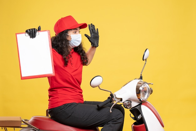 Front view female courier in mask holding file note on yellow background covid- job uniform worker service delivery