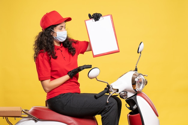 Front view female courier in mask holding file note on yellow background covid- job uniform worker service work pandemic delivery