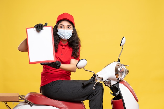 Front view female courier in mask holding file note on yellow background covid- job uniform worker work pandemic delivery