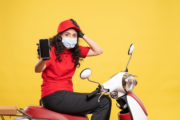Front view female courier in mask holding phone on the yellow background covid- job uniform worker service pandemic delivery
