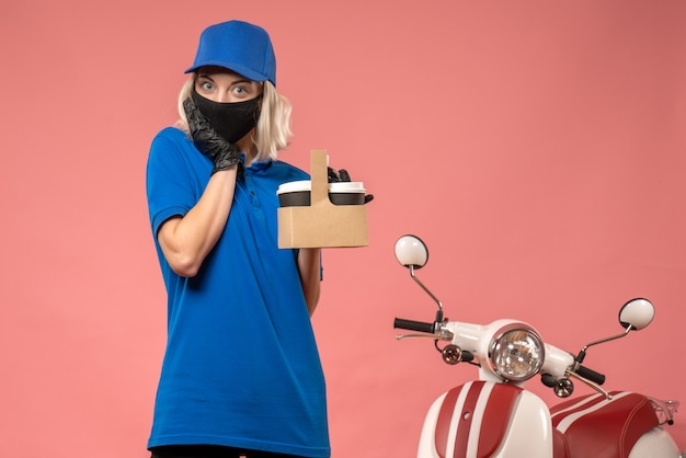 Front view female courier in mask with coffee cups on a pink