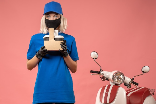 Front view female courier in mask with coffee cups on pink