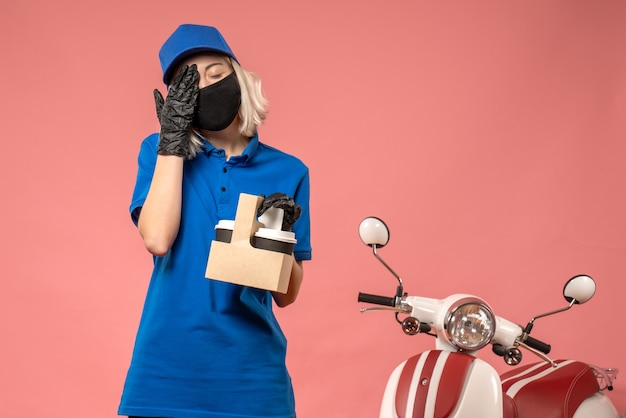 Front view female courier in mask with coffee cups on the pink