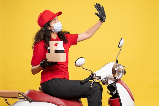Front view female courier in mask with coffee cups on yellow background covid- job delivery uniform service work