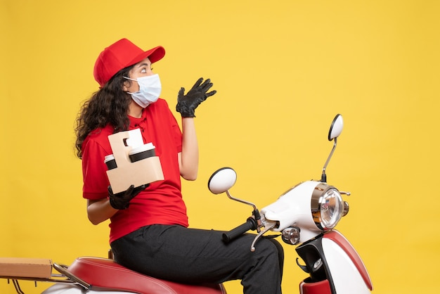 Front view female courier in mask with coffee cups on yellow background covid- job delivery uniform worker work