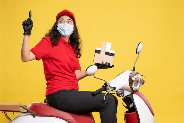 Front view female courier in mask with coffee cups on yellow background covid- job delivery uniform worker