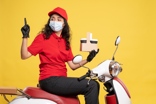 Front view female courier in mask with coffee cups on the yellow background service covid- job delivery uniform worker