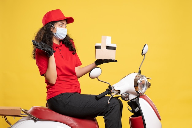 Front view female courier in mask with coffee cups on yellow background service covid- job uniform worker