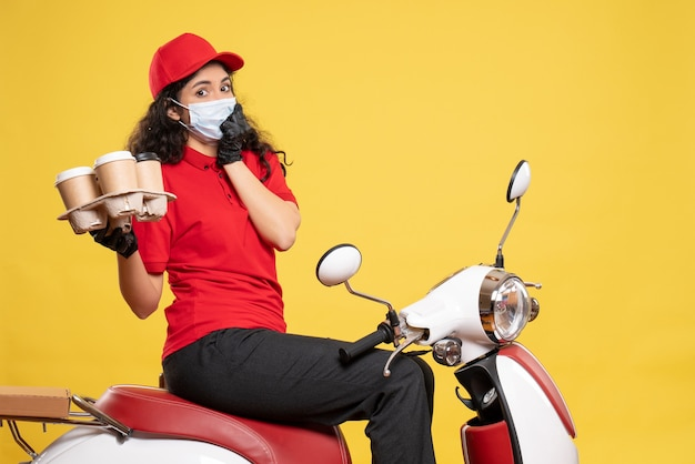 Front view female courier in mask with coffee cups on yellow background service pandemic worker delivery covid- job