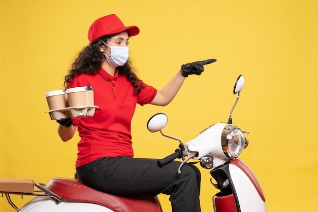 Front view female courier in mask with coffee cups on yellow background service pandemic worker uniform covid- job delivery