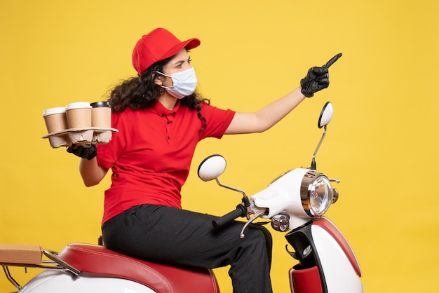 Front view female courier in mask with coffee cups on the yellow background service pandemic worker uniform delivery covid- job
