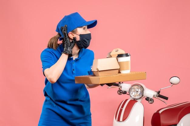 Corriere femminile vista frontale in maschera con consegna caffè e cibo sul rosa
