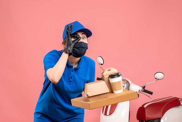 Front view female courier in mask with delivery coffee and food on pink