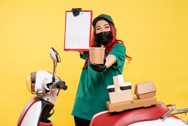 Vista frontale del corriere femminile in maschera con consegna caffè e cibo sulla parete gialla