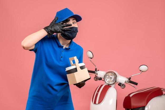 Corriere femminile di vista frontale in maschera con caffè di consegna sulla rosa