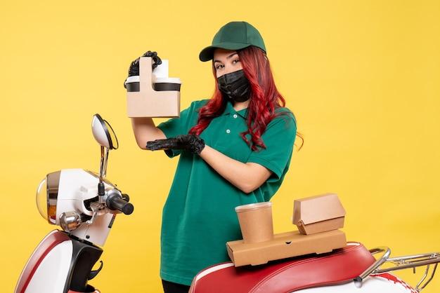 Vista frontale del corriere femminile in maschera con caffè di consegna sulla parete gialla