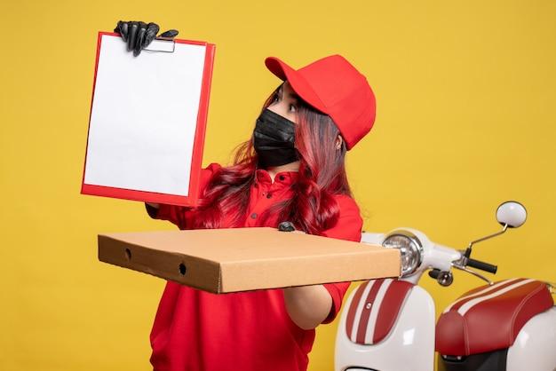 Vista frontale del corriere femminile in maschera con scatola di cibo di consegna e nota di file sulla parete gialla