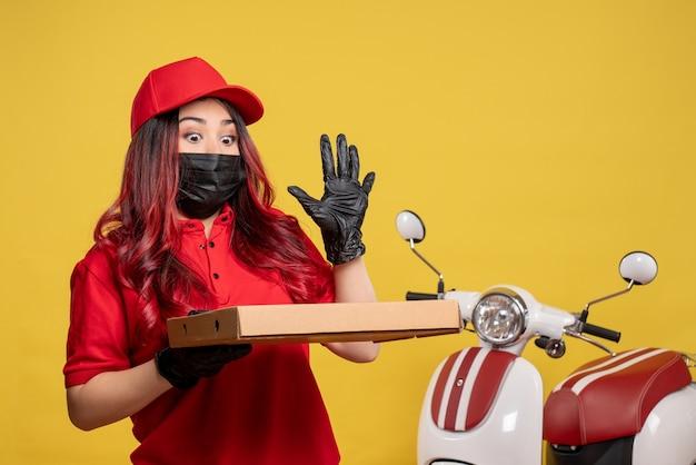 Vista frontale del corriere femminile in maschera con scatola di cibo di consegna sulla parete gialla Foto Gratuite