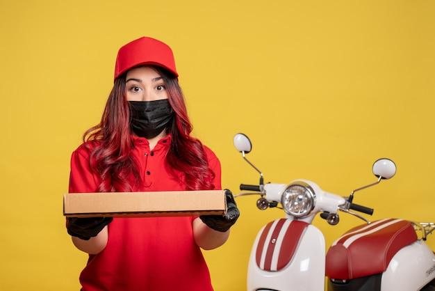 Vista frontale del corriere femminile in maschera con scatola di cibo di consegna sulla parete gialla