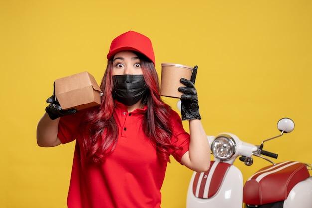 Vista frontale del corriere femminile in maschera con cibo di consegna e dessert sulla parete gialla