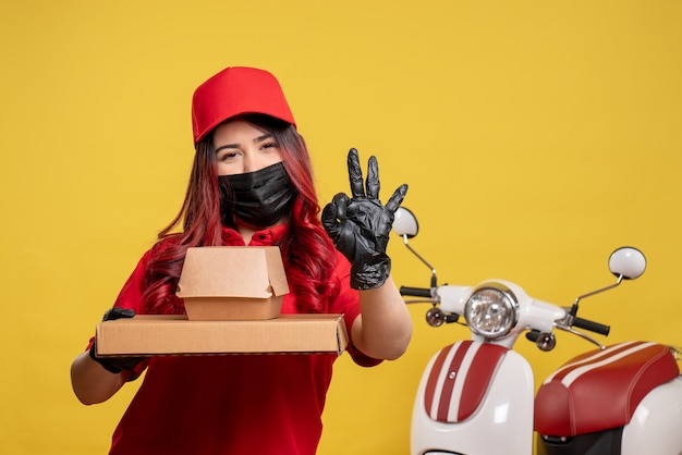 Front view of female courier in mask with delivery food on the yellow wall