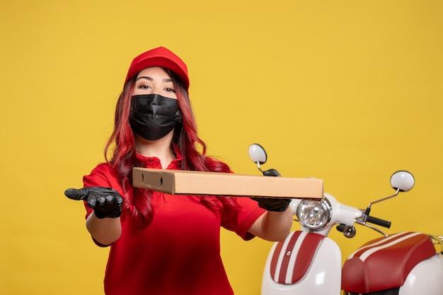Vista frontale del corriere femminile in maschera con cibo di consegna sulla parete gialla